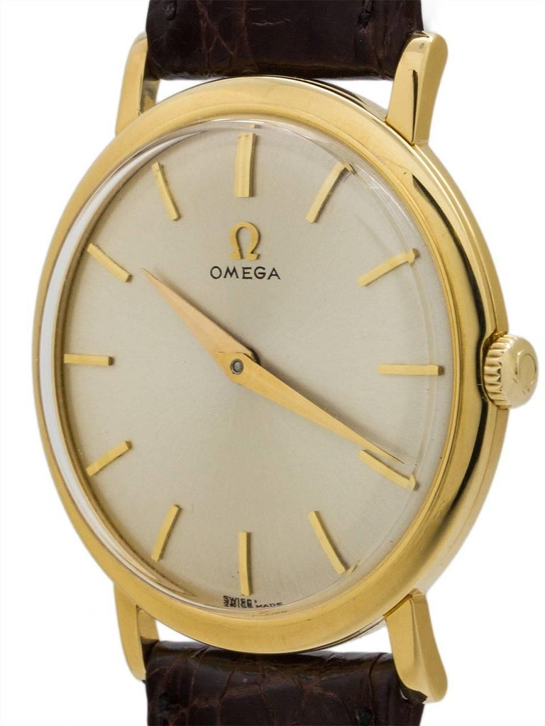 Vintage man's Omega 18K yellow gold dress model with thin, straight lugs, circa 1958. The thin dress case is 32mm in diameter, and features a signed gold Omega crown and acrylic crystal. With very minty condition original silvered satin dial with
