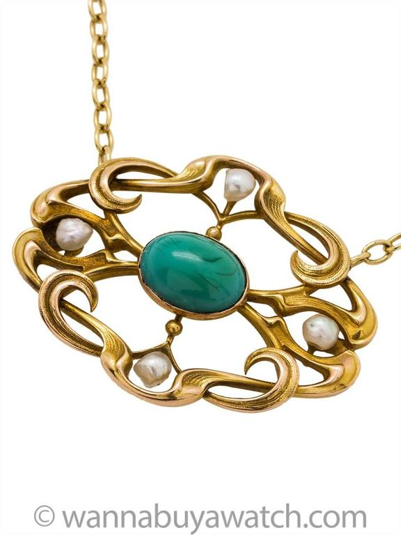 "Art nouveau necklace crafted in a 14k yellow gold featuring 4 natural pearls approx 4mm each and bezel set. 9 x 12mm oval blue turquoise center set in curvaceous open frame work. 28 x 38mm on 18"" oval link chain. Very lovely antique"