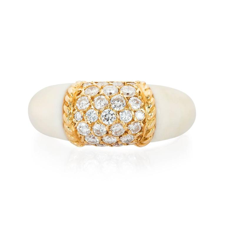 A rare white coral 'Philippine' ring by Van Cleef & Arpels, the larger than usual ring set to the centre with 27 round diamonds framed by a gold ropetwist border and flanked by white coral shoulders. Set in 18KT yellow gold. Signed and numbered,