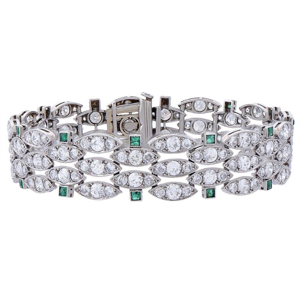 A diamond, emerald and platinum bracelet, French, composed of articulated, marquise-shaped links set with round brilliant-cut diamonds, flanked on alternate rows by pairs of small, square-cut emeralds, all mounted in platinum, to a concealed clasp