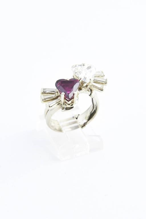 The style of this ring represents the French saying Toi et Moi which means that the ruby and diamond hearts represent you and me.  This exceptional rings features a heart shaped 1.44 carat diamond (GIA Cert H,SI2) and approximate 1.50 carat heart