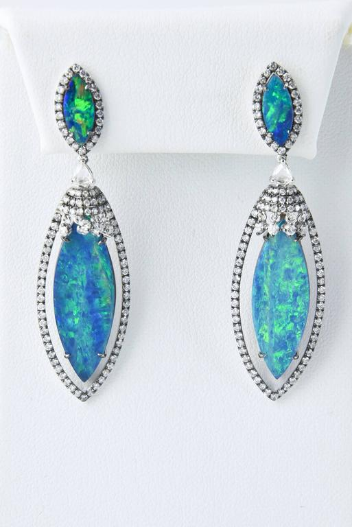 Stunning Well Matched Opal Doublet Earrings mounted in 18 karat white gold accented with 1.82 carats of diamonds.