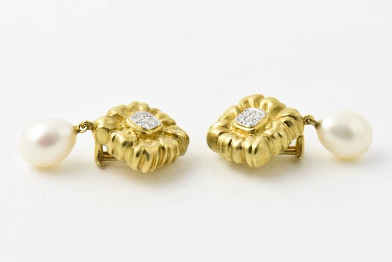 """Finely made three dimensional 18k gold flowers ear clips with four diamonds in the center of each.  The flowers are .88"""" in either direction with a beautiful white south sea pearl teardrop dangling from them.  The pearls  are approximately"""