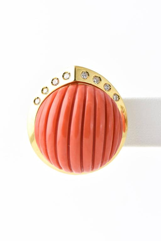 Large ribbed coral cabochon with diamond accents in an 18k yellow gold frame.  It sits on the ear and is hold in place with a post and clip.