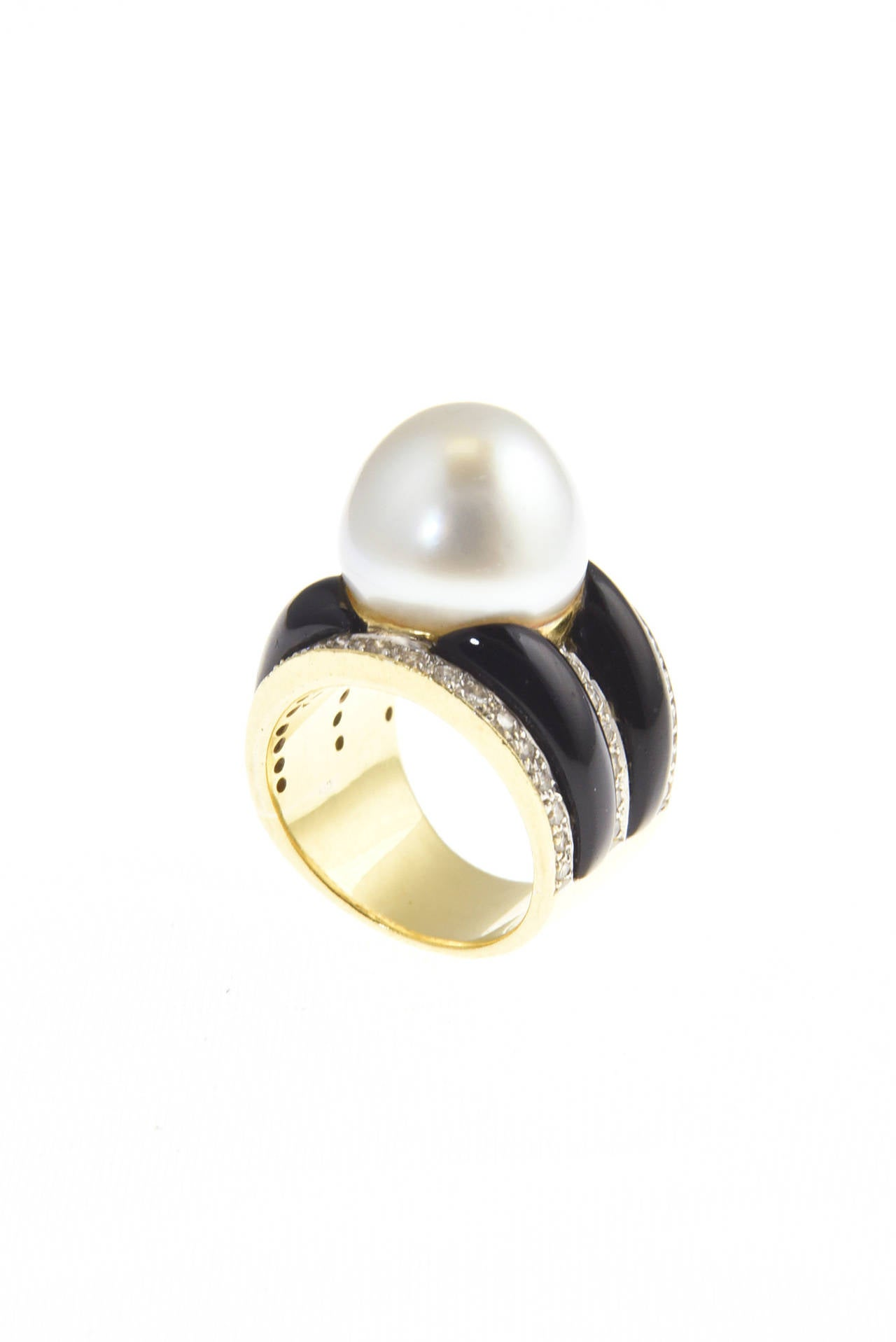 Finely made ring with clean classic lines featuring a South Sea Pearl center with interchanging diamond and onyx stripes mounted in 18k yellow gold.