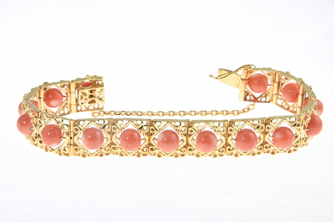 This bracelet features 18k yellow gold stylized links that each have a coral bead in the center.  The links are hinged together.  It is approximately 6.76