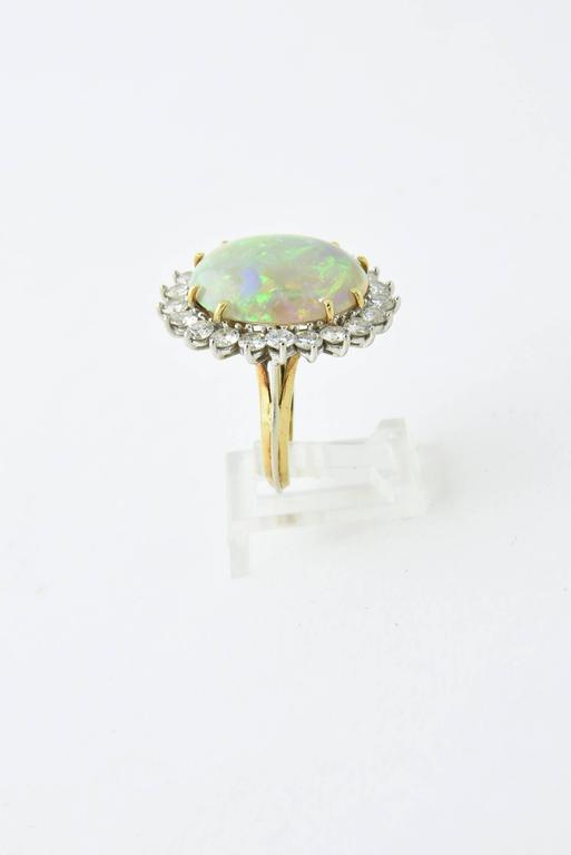 Semi-black Crystal Opal with incredible color with a diamond frame mounted in 18k white & yellow gold.  17.5 carat approximate weight of opal and 2.52c approximate total weight of fine quality diamonds.