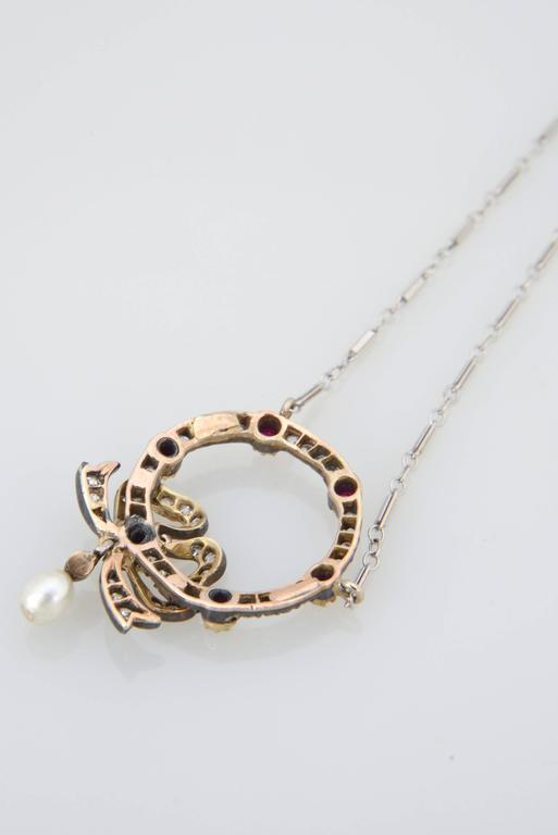 A rare and delicately crafted antique turn of the century Edwardian Belle Époque necklace pendant with an emblematic for that period bow design. The pendant is made of silver on gold with the gems set in silver. Finished with a very nice and fine