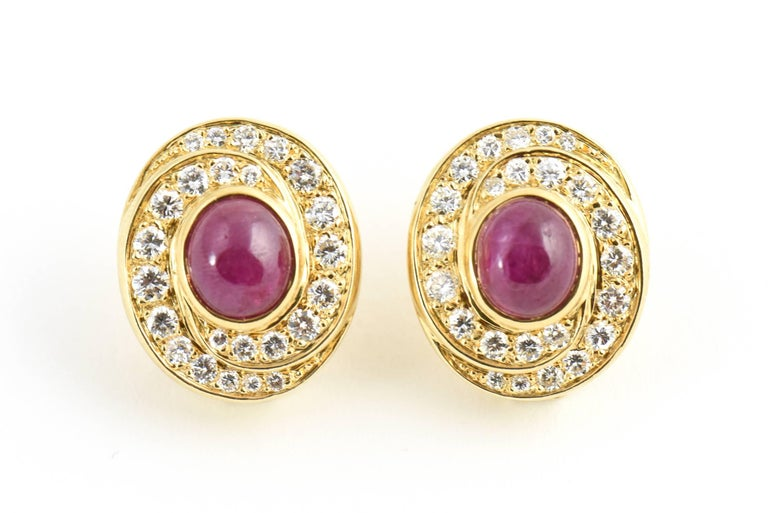 Pave diamonds swirl around a 5c Burma ruby in each of these earrings set in 18k yellow gold.  They have a clip back with NO post.