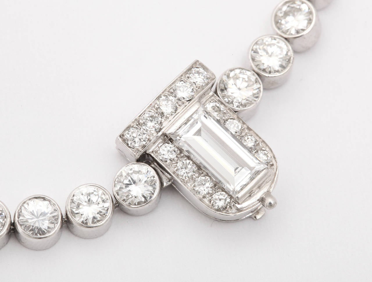 Platinum and bezel set rivière necklace with a central large baguette cut  diamond clasp.  The clasp has a concealed pendant loop on the back, allowing for a drop or pendant to be hung.