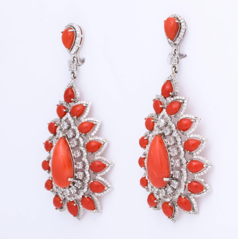 18kt white gold, coral and diamond (4.49cts) earrings.  Perfectly matched, bright orange coral pear shape cabochons are each surrounded by diamonds.  The delicate setting makes these earrings appear to float just below the ear.