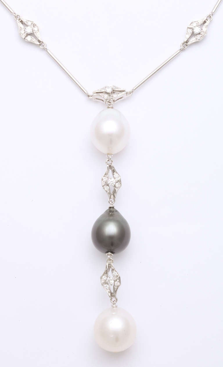 This necklace is a beautiful design in contrasting black and white.  Highly polished white gold set with white diamonds are offset with a singularly impressive 13.5mm Tahitian black pearl.  The two white pearls measure 13.8 and 14mm and there are