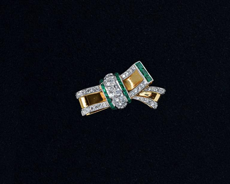 Lovely, unique Retro 18 karat gold bow ring containing round brillinat-cut diamonds and accented by baguette-cut calibre emeralds.  Currently fitted with an internal ring guard but can be sized to fit any finger.