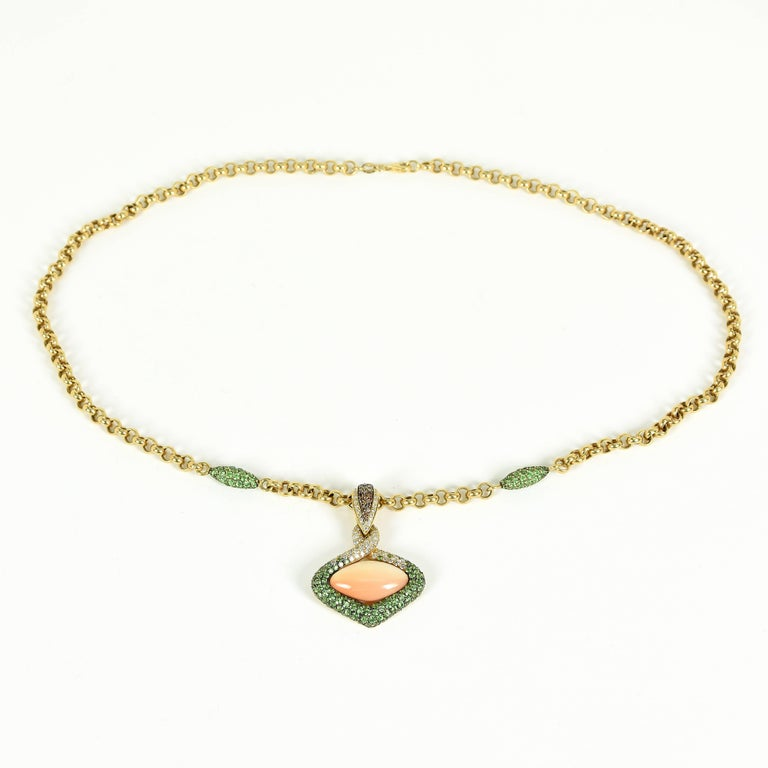 18ct gold modern enhancer in an oval shape.  The centre of the oval is rub set with an marquise en cabochon cut pink synthetic hydro carbon and pavé set on the surround with diamonds and garnets.