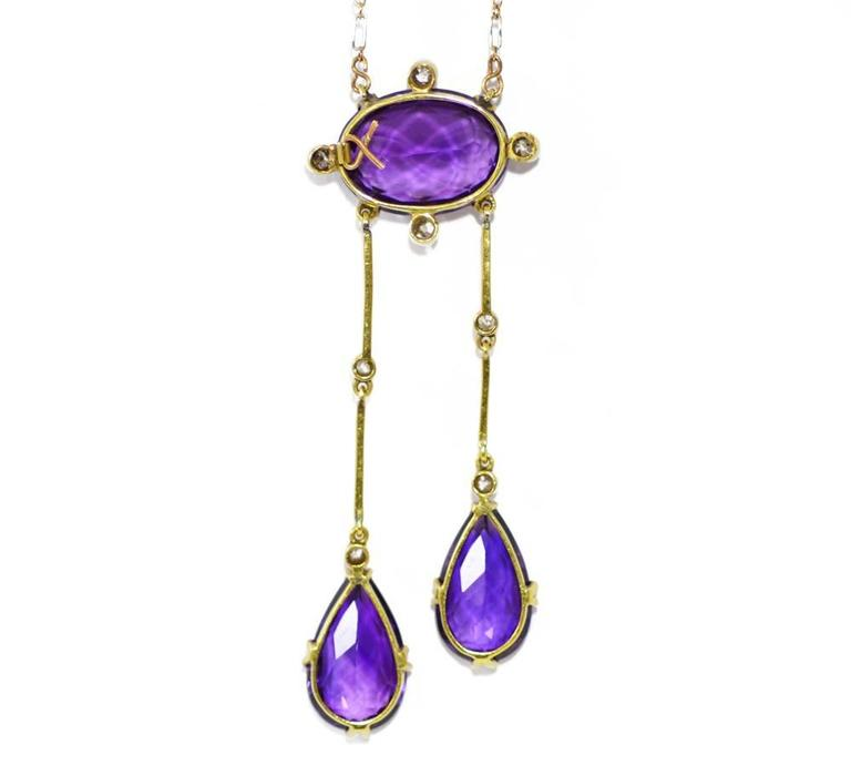 An Edwardian amethyst and diamond articulated pendant, the principal oval amethyst suspending two amethyst drops, mounted in platinum and 18ct yellow gold.