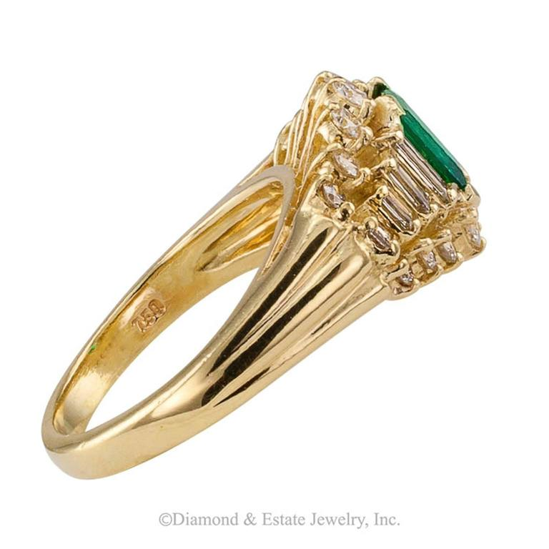 Emerald-cut Emerald Diamond Gold Ring  1980s fine emerald and diamond yellow gold ring.  The elegant 18-karat yellow gold design centers upon a very fine emerald-cut emerald weighing 0.61 carat, between stepped and tapering shoulders set with