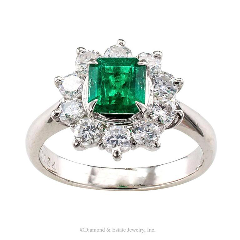Emerald Diamond Halo Platinum Ring  Emerald and diamond halo platinum ring circa 1990.  Centering a fine emerald-cut Colombian emerald weighing 0.76 carat within a halo of round brilliant-cut diamonds totaling approximately 0.84 carat, approximately