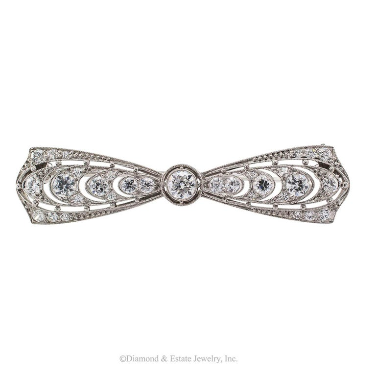 T B Starr Edwardian Diamond Platinum Bow Brooch  T B Starr Edwardian diamond and platinum bow brooch circa 1910.  Designed as a bow centering an old-cut diamond flanked by outwardly graduating similarly cut diamonds, on a platinum mounting that is a