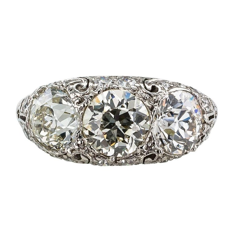 Edwardian Old European Cut Three Stone Diamond Platinum Ring  Edwardian 1910 old European-cut three stone diamond and platinum ring.  The design showcases three large old European-cut diamonds together weighing approximately 3.00 carats,