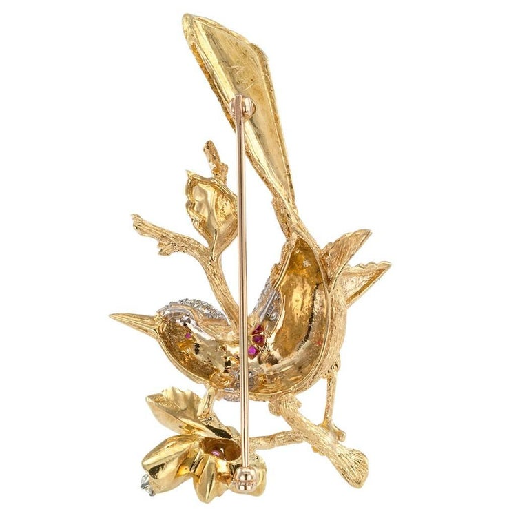1960s bird brooch with diamonds rubies and 18 karat gold.  Designed as a perky bird perched on a flowering branch, both set with rubies and diamond, the diamonds totaling approximately 0.75 carat, approximately G - H color and VS clarity.  Artistic