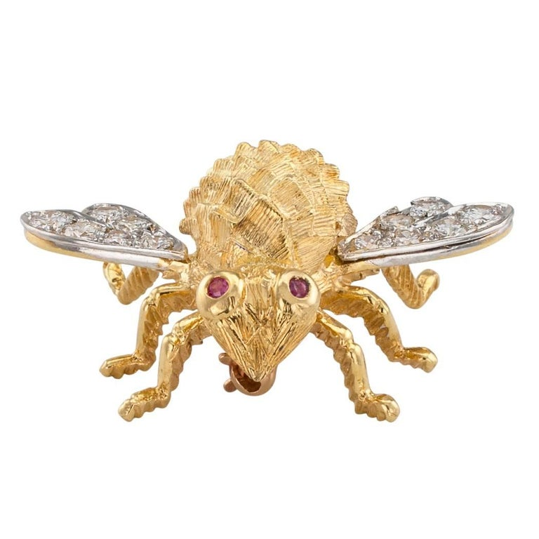 Rosenthal 1970s diamond ruby and gold honey bee brooch. Mounted in 18-karat gold, the wings set with round brilliant-cut diamonds totaling approximately 0.70 carat, approximately G color and VS clarity, ruby-set eyes to the body accentuated by a