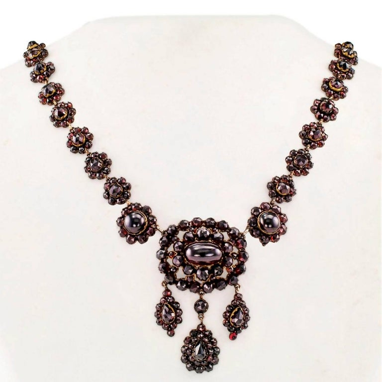 Victorian 1880s gilded silver garnet necklace. Set throughout with very red cabochon and faceted garnets, in a series of graduated links designed as flowers connected to a larger central medallion suspending three teardrop-shaped motifs. The antique
