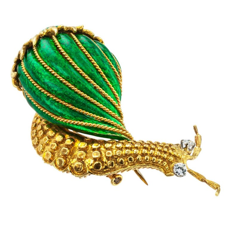 David Webb diamond and enamel 18 karat gold snail clip brooch circa 1980.  The figural design features a representation of a snail in forward march carrying its striped, brilliant green enameled shell embellished with corded gold, the diamond-set