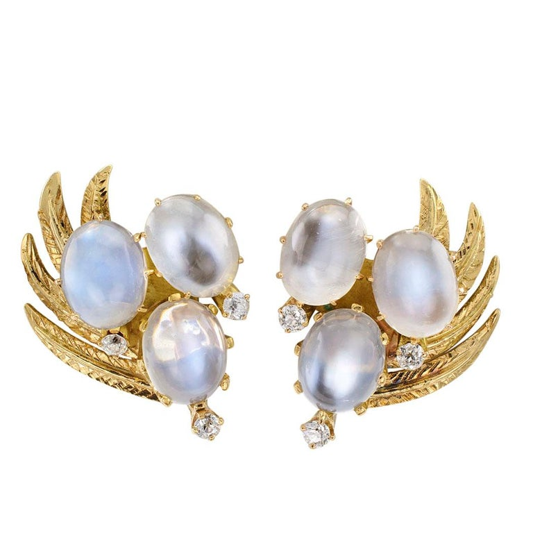 Moonstone and diamond gold ear clips circa 1950. The left and right matching designs feature trios of luminous moonstones and sparkling diamonds arranged over a spray of gold leaves motif, mounted in 14-karat gold. These earrings are a smart size,