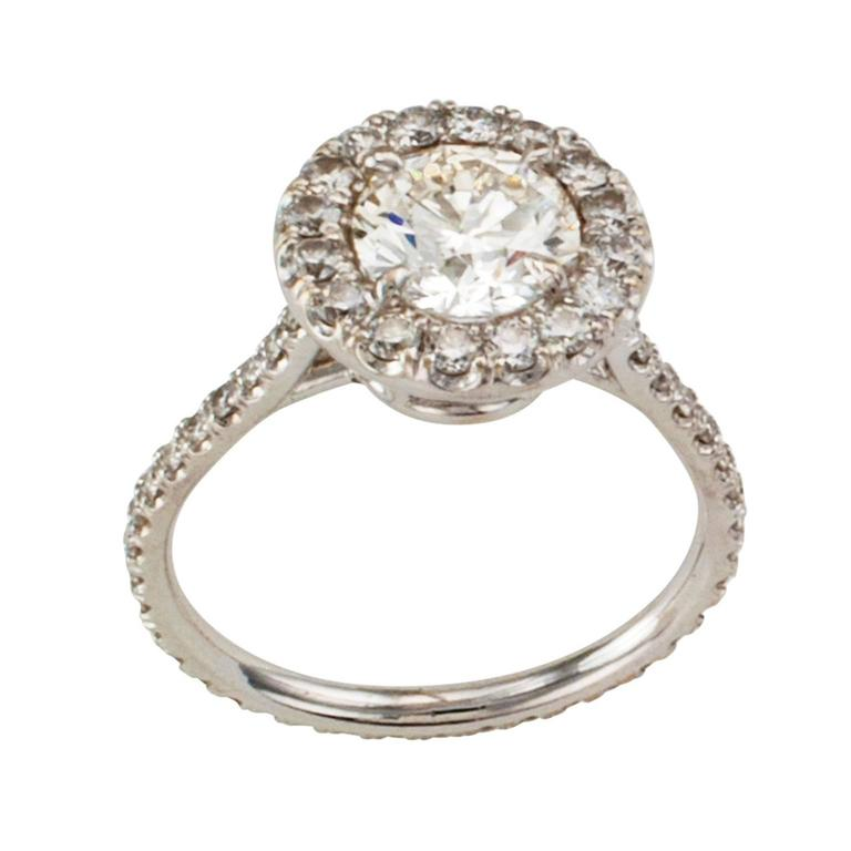 Estate Diamond Halo Engagement Ring  An exciting and more contemporary halo engagement ring beautifully crafted in 18 karat white gold featuring a round brilliant-cut diamond weighing approximately 1.20 carats, approximately J - K color and SI1