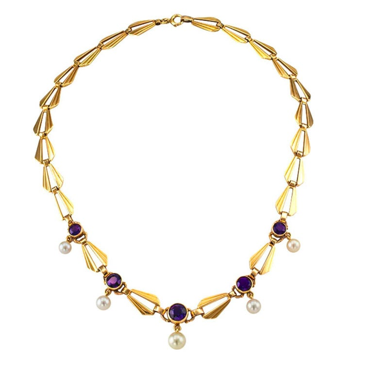 Retro Amethyst and Cultured Pearl Gold Necklace Circa 1950  Decorated on the front by five bezel-set round amethyst, each suspending a round cultured pearl ranging from 7 – 5.5 mm, connected by elongated, open and fluted links, mounted in 14-karat