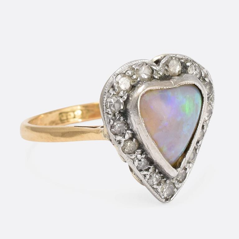 This beautiful antique ring is modelled with a heart-shaped head, set with diamonds and a heart-shaped opal. The simple band is crafted from 18ct yellow gold, with the stones set in silver. The back of the head is nicely galleried, allowing light in
