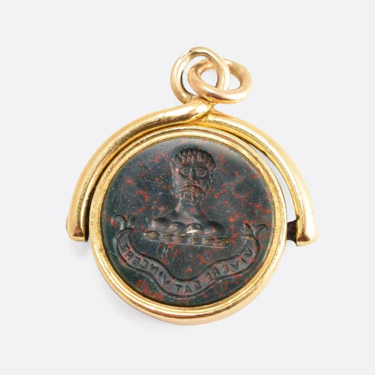 This attractive antique spinner fob is set with two carved stone panels: one bloodstone, the other carnelian agate. Each panel is carved with a heraldic crest, above Latin motto. The words read