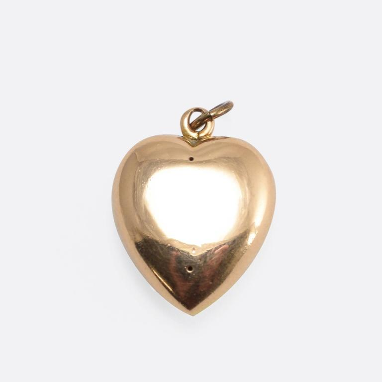 This pretty antique heart pendant is pavé set with seed pearls. It's modelled in 15k yellow gold, and dates to the late 19th Century. The word pavé is French, and literally translates to English as