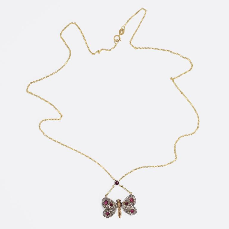 This adorable antique necklace is fashioned as a diamond-studded butterfly, with vibrant ruby accents. The butterfly itself is likely of Russian origin, and came to us as a pin brooch. Our jeweller has added a 9k yellow gold chain, with a further