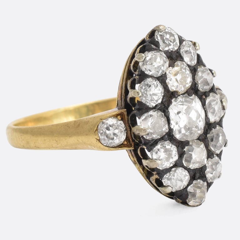 A splendid antique old cut diamond cluster ring, with marquise-shaped head and diamond shoulder accents. It dates to the Victorian era, c.1880, set with just over 2 carats of bright old mine cuts. The band is modelled in 18k yellow gold, and the
