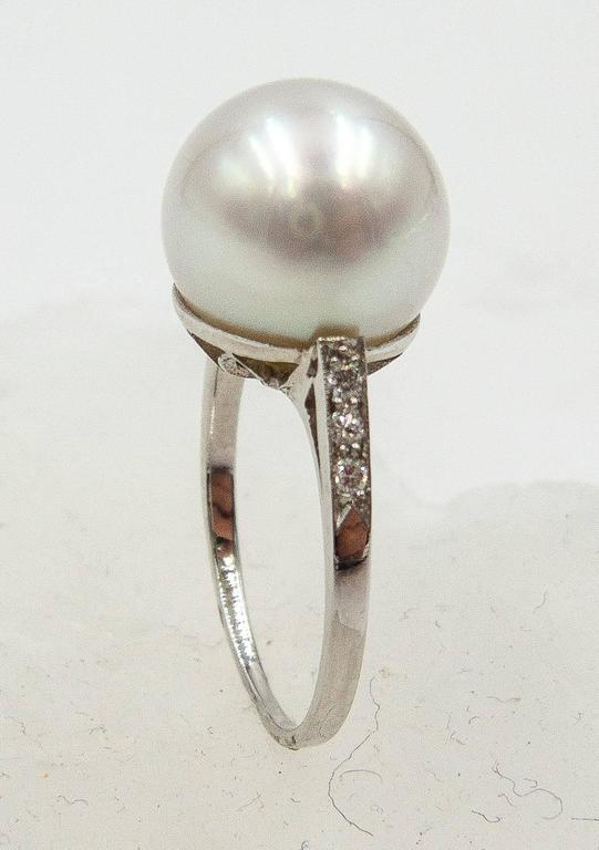 Classic elegance in a pearl and diamond ring.   A  full,softly lustrous white South Sea pearl measuring 11.5 millimeters sits atop a handmade platinum mount, the shoulders accented with petite full cut diamonds.   This is a ring that is timeless and