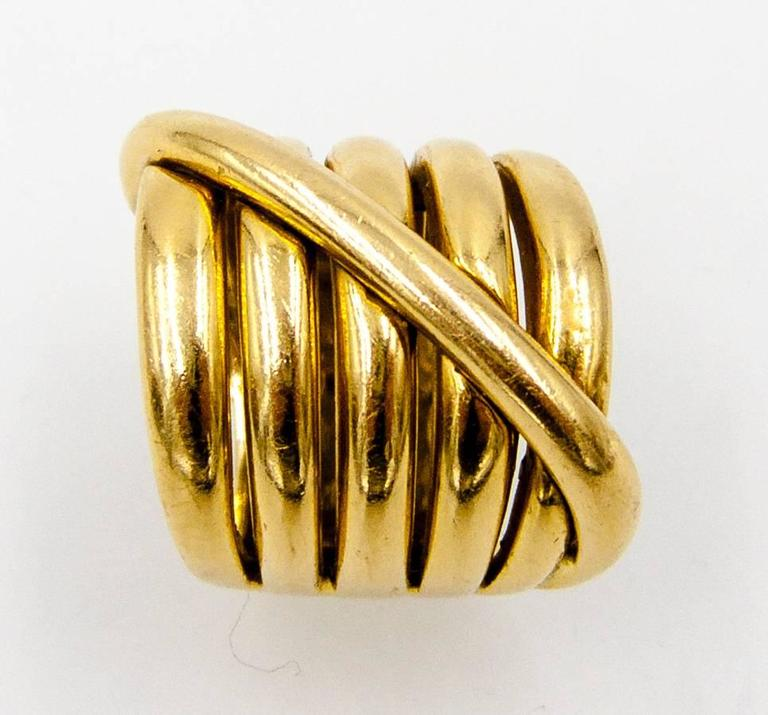 "Elegantly sleek and stylishly Italian, this unusual ring is an attention-grabber in its own quiet way.   It glides 3/4"" up and down the finger, and the five domed rows of 18 karat gold are bisected on the diagonal by an additional rope of"