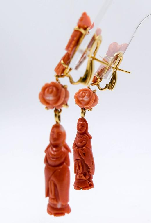 For coral lovers and shoulder duster lovers alike, these distinctive earrings display an interesting range of coral colors.  The Quan Yin statues at the base are a deep and rich orange, while the central flowers are a more delicate shade.  The