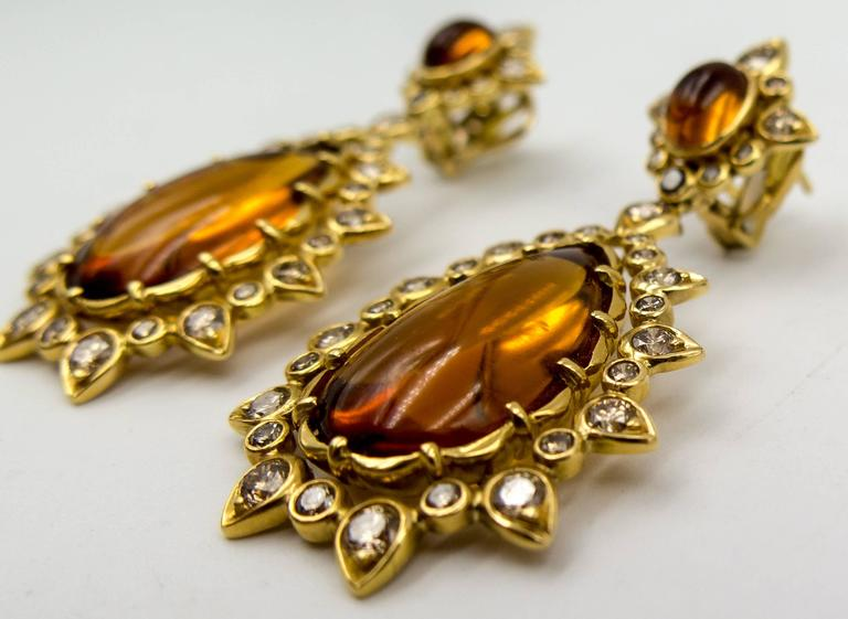 Marilyn Cooperman jewelry is instantly recognizable from across the room:  bold, distinctive, edgy, and yet elegantly feminine.   These unique earrings contain large expanses of domed, honey colored citrine at the top and bottom, accented by