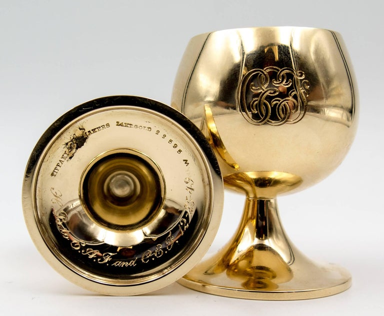 """An unusual and highly personal pair of solid 14 karat gold Tiffany & Co cups certainly intended for several special Christmas holidays.   The cups stand 2"""" high and 1 1/2"""" across at the base, the surfaces highly polished and"""