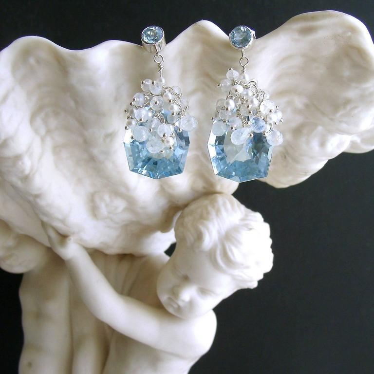 Sparkling fancy-cut blue topaz have been adorned with cascading tendrils of hand-linked minuscule seed pearls and flashy moonstone rondelles and briolettes, while suspended from simple blue topaz post earrings.  The delicate nature of these earrings