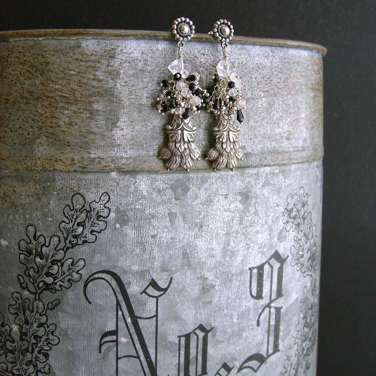 Airella Earrings.  A cascade of hand-linked rock crystal, mystic moonstone, silver pyrite and glossy black spinel tendrils - tumble down upon sterling silver lion's paw amulets to create these heraldic earrings.  The simplicity of the oxidized