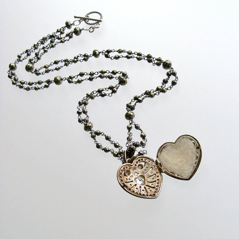 Saint Esprit II Heart Necklace.  A double strand of hand linked pyrite with a Victorian silver paste heart vinaigrette is paired with other layering necklaces revolving around the French theme of the Saint Esprit Dove.  The darling little heart