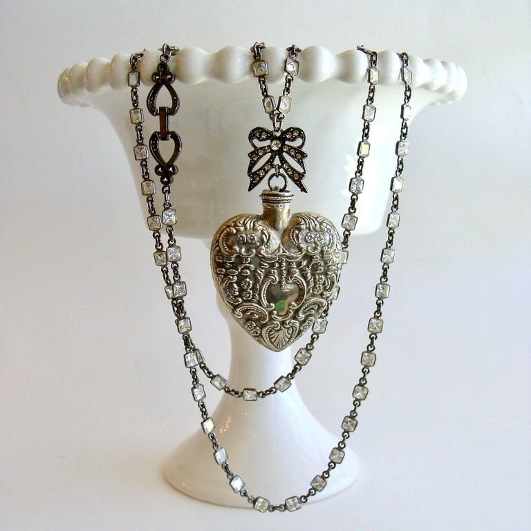 Cressida Necklace.  A lovely antique sterling silver repousse chatelaine heart scent bottle is the focal point of this beautiful layering necklace.  A charming rhodium silver paste bow presides over the top of the feminine heart shaped bottle, while