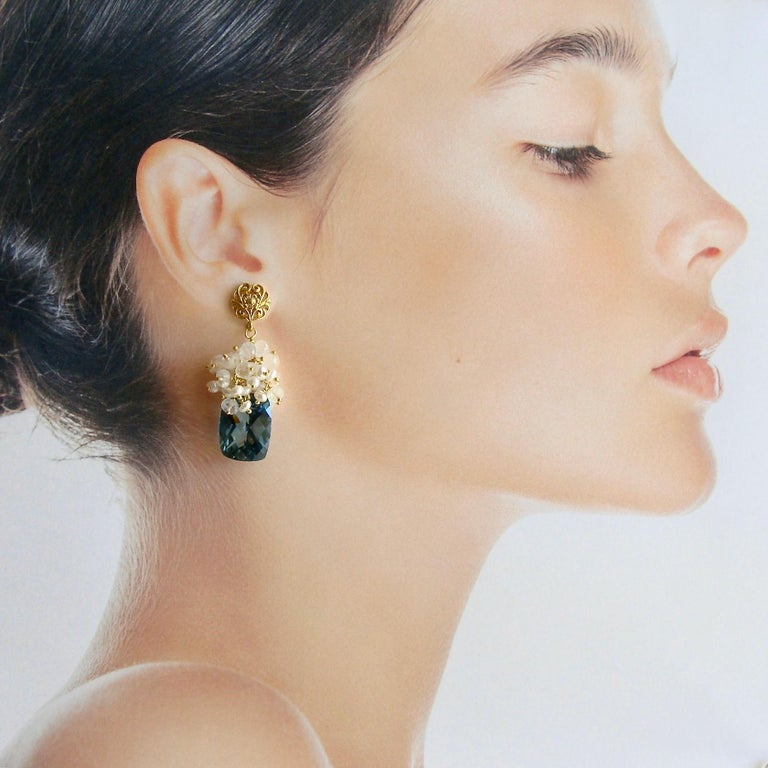 Dione VIII Earrings.  These stunning earrings were named after one of the Greek Nereides or sea goddesses – Dione (The Divine).    Reminiscent of the ocean – Luxe harlequin faceted London blue topaz baguettes are capped with a foamy froth of dainty