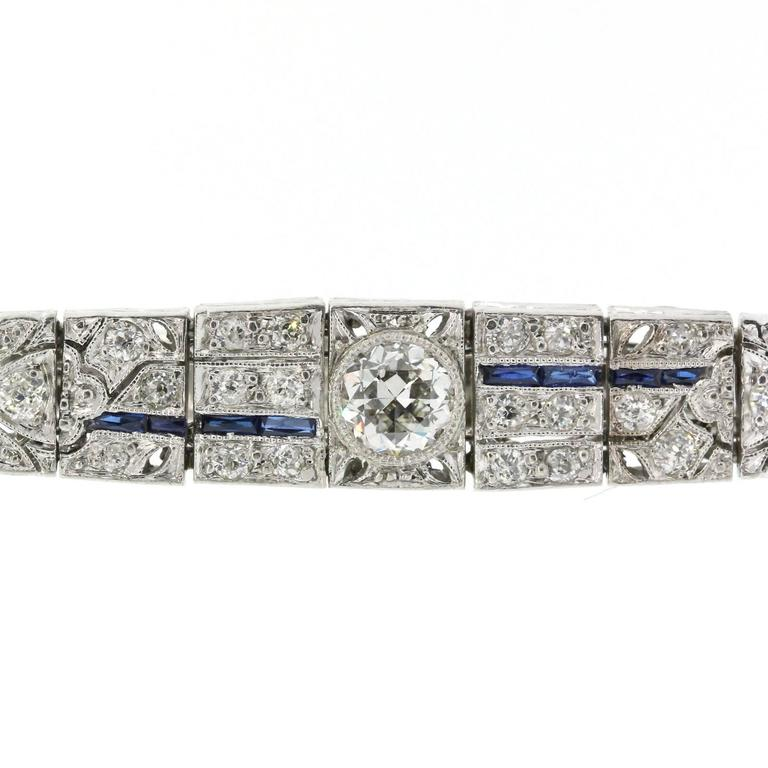 Coveted tapered Art Deco bracelet of box designed links and open work, featuring a bezel set Old Cut Diamond in center, and flashing over three carats of Old European Cut Diamonds. The delicate design work is accented with original synthetic