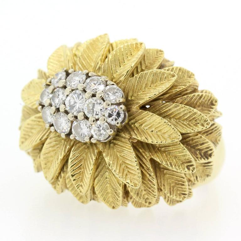 A 1960's 18KT yellow gold ring centering a cluster of thirteen Round Brilliant Cut Diamonds with cascading palm leaves.  Pretty!