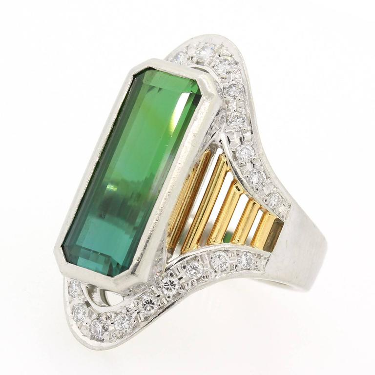 A stylish  platinum and 18KT yellow gold ring featuring an elongated 7.53 carat Green Tourmaline.   The ring is accented with Round Brilliant Cut Diamonds and enhanced with yellow gold open work. Impressive and Fun Ring!
