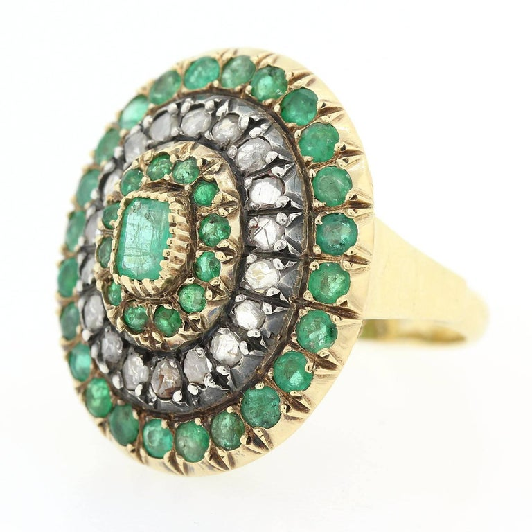 A playful oval shape 18KT gold and Silver ring, accented with a Rectangular Cut Colombian Emerald.  The Emerald is surrounded by twelve small Emeralds and two rows of  twenty Rose Cut Diamonds and twenty four Emeralds.  The setting is enhanced with
