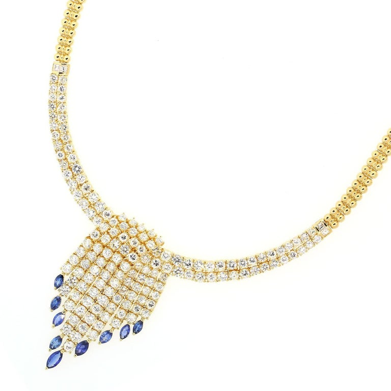 A tassel design 18KT yellow gold necklace with 16.95 carats of sparkly Round Brilliant Cut Diamonds.  This unique necklace features cascading Diamonds dropping  3.05 carats of Blue Sapphires.  The necklace has a
